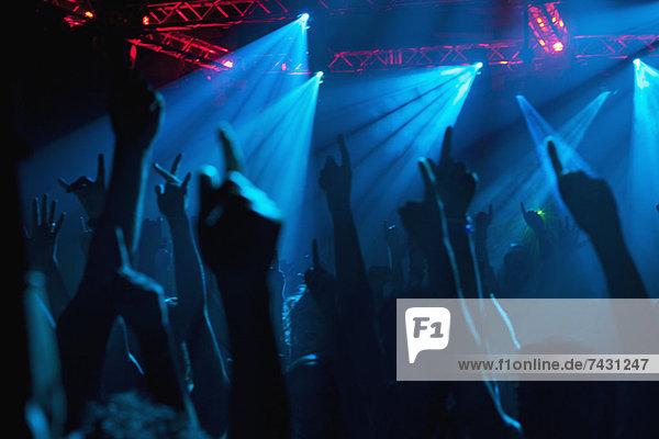 Silhouette der jubelnden Menge mit erhobenen Armen beim Konzert