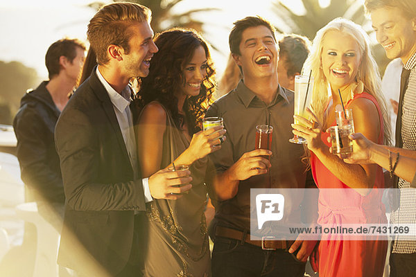 Lachende Freunde trinken Cocktails auf dem sonnigen Balkon