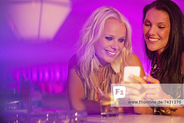 Lächelnde Frauen  die auf das Handy im Nachtclub herabblicken
