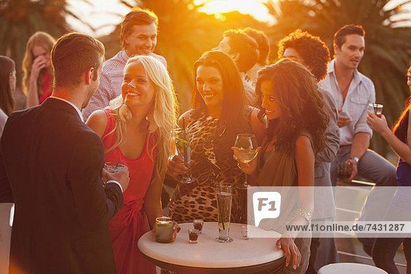 Lächelnde Freunde trinken Cocktails auf dem sonnigen Balkon