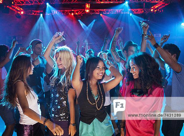 Lächelnde Freunde tanzen auf der Tanzfläche des Nachtclubs