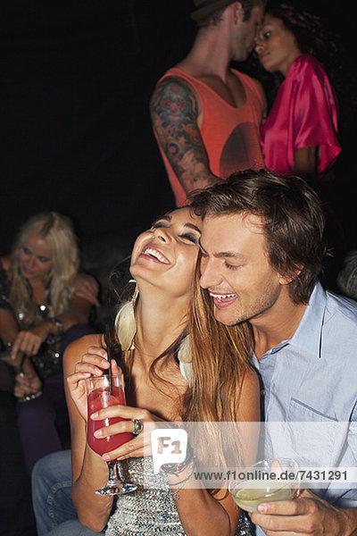 Lachendes Paar beim Umarmen und Trinken von Cocktails im Nachtclub