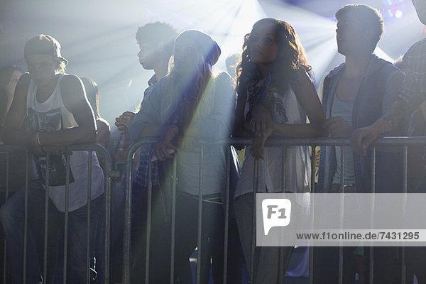 Menschenmenge lehnt sich beim Konzert an das Geländer