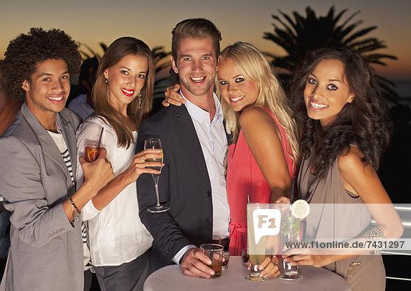 Porträt von lächelnden Freunden  die bei Sonnenuntergang Cocktails auf dem Balkon trinken.