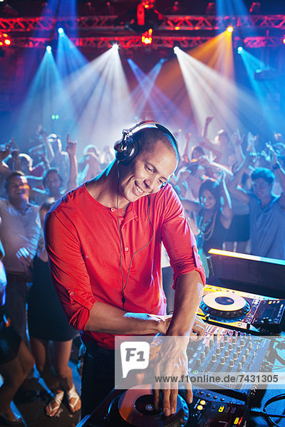 DJ at turntable with crowd on dance floor in background