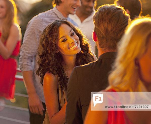 Lächelnde Frau im Gespräch mit dem Mann auf dem sonnigen Balkon
