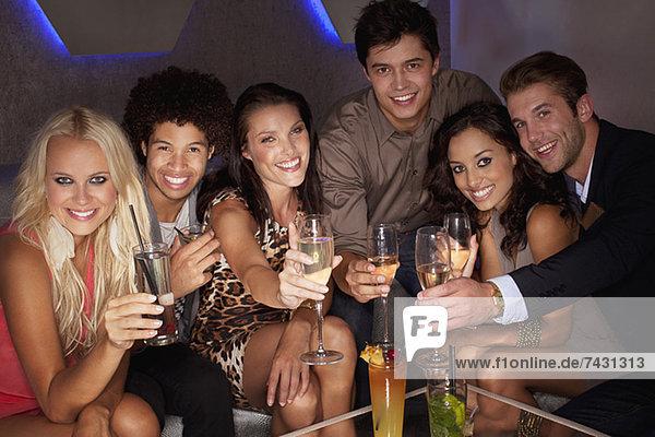 Porträt von lächelnden Freunden  die Cocktails im Nachtclub toasten.