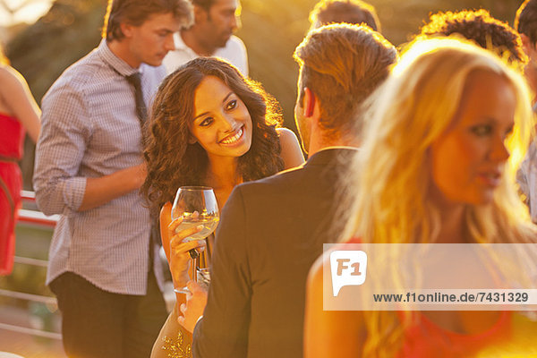 Lächelnde Frau mit Weinglas im Gespräch mit dem Mann auf dem sonnigen Balkon
