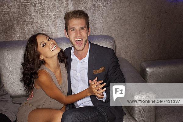 Porträt eines begeisterten Paares  das auf dem Sofa im Nachtclub Händchen hält.