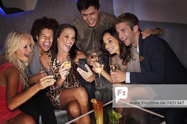 Lächelnde Freunde trinken Cocktails und schauen auf das Handy im Nachtclub.