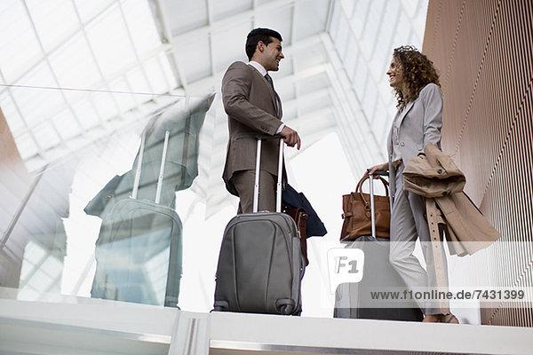 Lächelnder Geschäftsmann und Geschäftsfrau mit Koffern im Gespräch am Flughafen