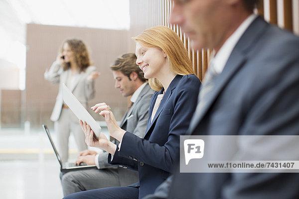 Geschäftsleute mit Laptop und digitalem Tablett