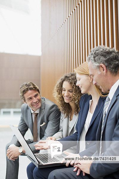 Lächelnde Geschäftsleute treffen sich mit Laptop