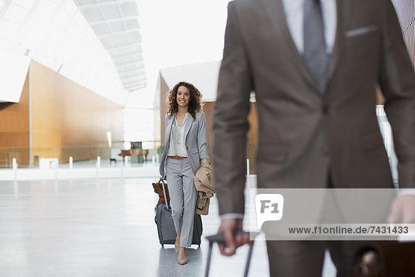 Lächelnde Geschäftsfrau beim Kofferziehen am Flughafen