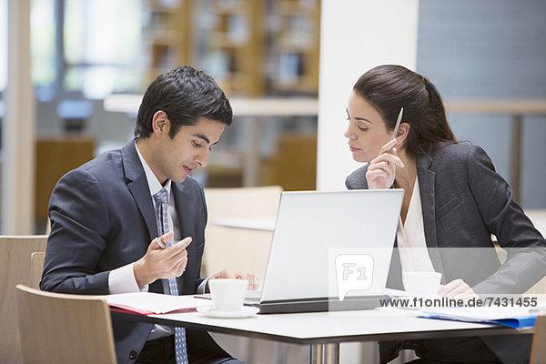 Geschäftsmann und Geschäftsfrau beim Durchsehen der Papiere im Cafe