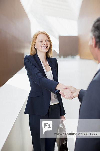 Lächelnde Geschäftsfrau beim Händeschütteln mit Geschäftsmann