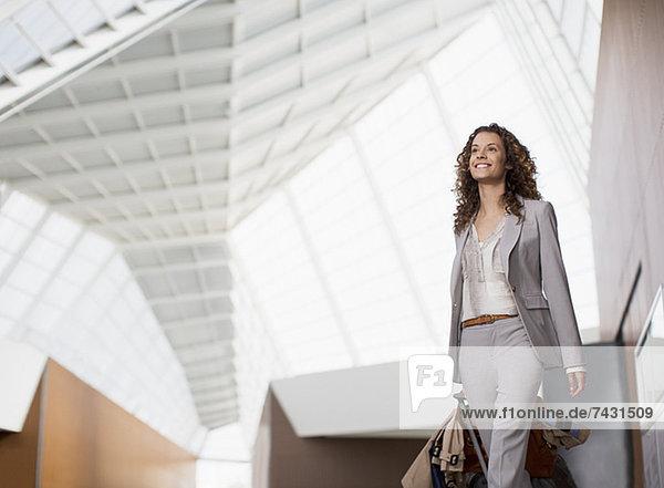 Lächelnde Geschäftsfrau mit Koffer am Flughafen