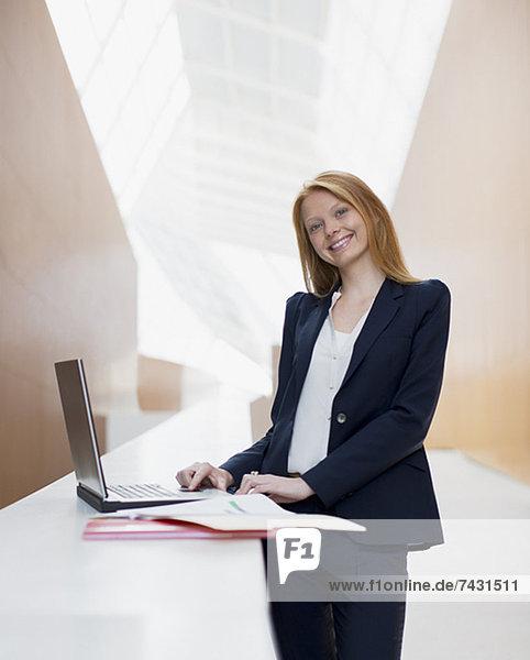 Porträt der lächelnden Geschäftsfrau mit Laptop im Büro