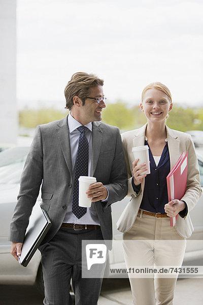 Lächelnder Geschäftsmann und Geschäftsfrau beim Gehen mit Kaffeetassen
