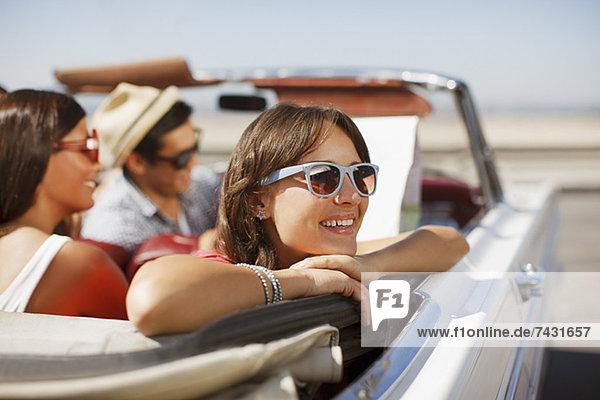 Lächelnde Frau  die sich aus dem Cabrio lehnt