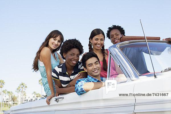 Lächelnde Freunde sitzen im Cabriolet