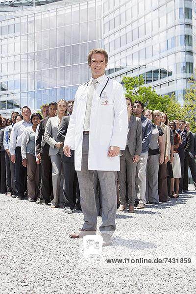 Porträt eines lächelnden Arztes mit Geschäftsleuten im Hintergrund