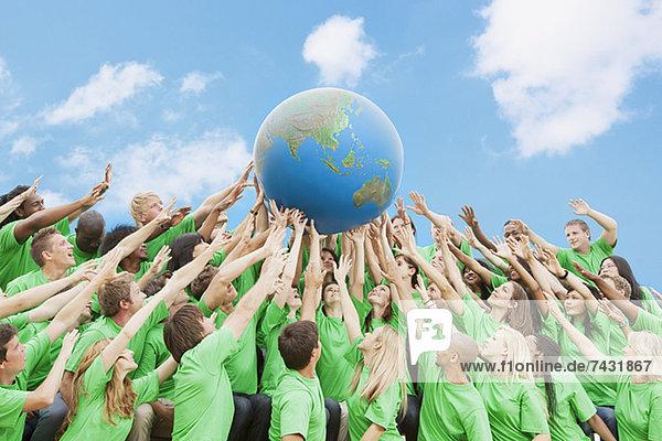 Team in grünen T-Shirts  die den Globus über Kopf heben. Team in grünen T-Shirts, die den Globus über Kopf heben.