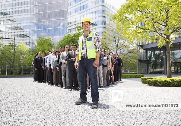 Porträt eines lächelnden Bauarbeiters mit Geschäftsleuten im Hintergrund