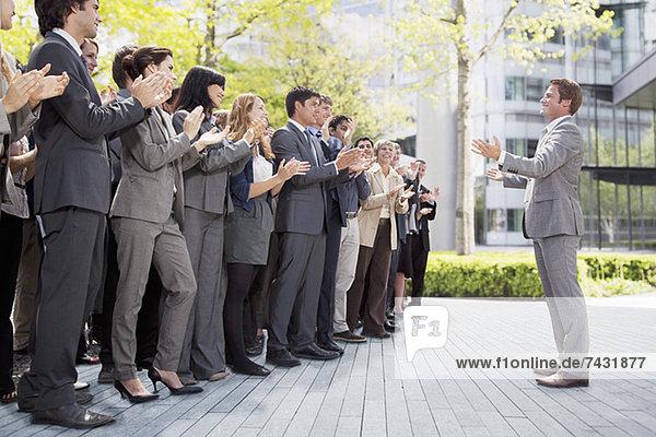 Die Menge der Geschäftsleute  die den Geschäftsmann anfeuern.