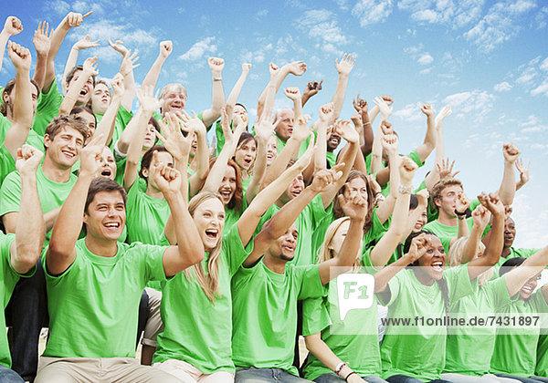 Menschenmenge in grünen T-Shirts jubelnd mit erhobenen Armen