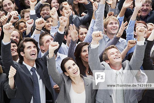 Lächelnde Menge von Geschäftsleuten  die mit erhobenen Armen jubeln.