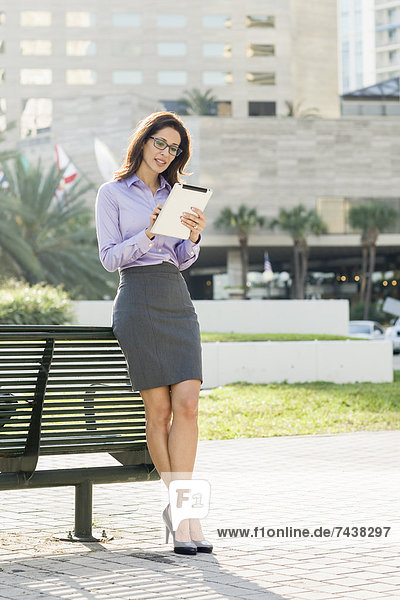 Hispanic businesswoman leaning on bench using digital tablet