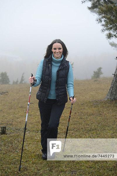 Brünette junge Frau macht Nordic Walking