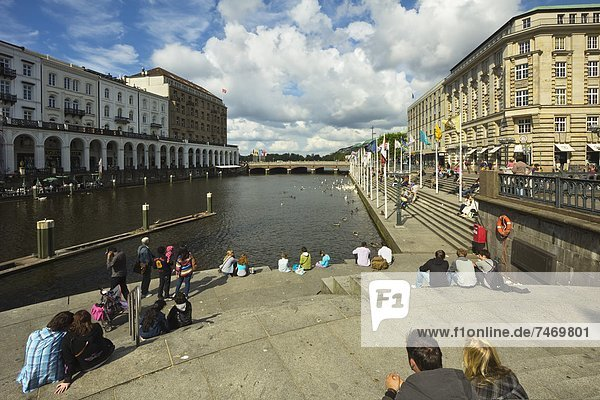 People sitting by the Alster River and the Reesendamm near the Rathausmarkt in this popular district of the city  Hamburg  Germany  Europe