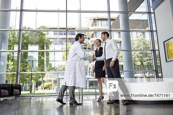 Arzt und Geschäftsmann beim Händeschütteln
