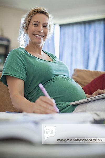 Schwangere Frau bei der Arbeit am Laptop