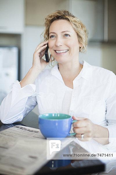 Frau mit Kaffee am Telefon
