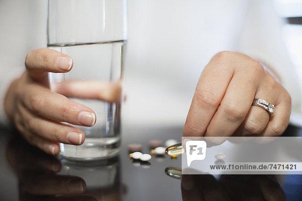 Nahaufnahme einer Frau,  die Vitamine einnimmt