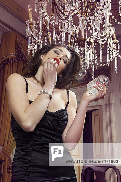 Frau in Dessous hält Glas