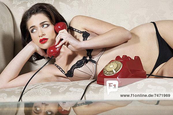 Frau in Unterwäsche spricht am Telefon