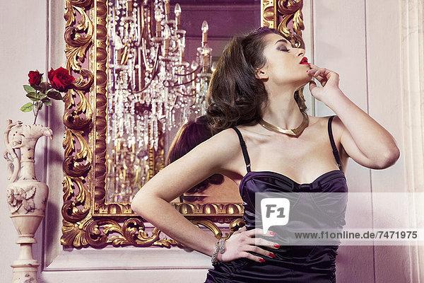Frau in Dessous am Spiegel stehend