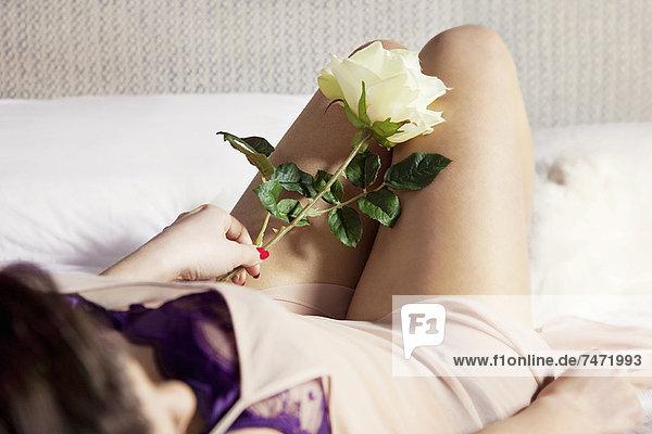 Frau in Dessous mit Blume auf dem Bett
