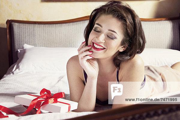 Frau in Dessous mit Geschenk auf dem Bett