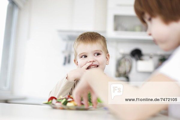 Kinder beim gemeinsamen Essen am Tisch