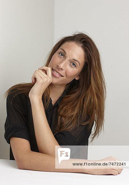 Lächelnde Frau am Schreibtisch sitzend