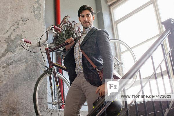 Mann mit Fahrrad im Treppenhaus