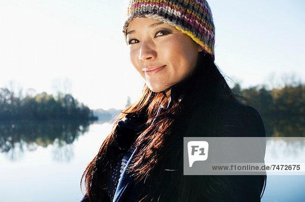 Woman standing by still lake