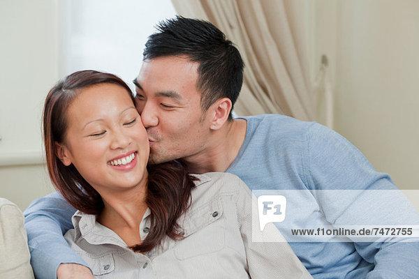 Lächelndes Paar auf dem Sofa küssend