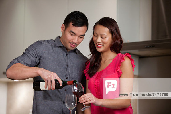 Couple having wine together in kitchen