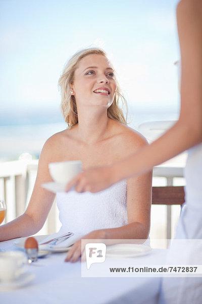 Frau beim Frühstück im Freien